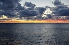 Solnedgång över havet till och med moln Arkivfoton