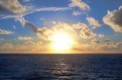 Solnedgång över havet till och med moln Arkivbild