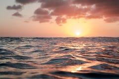 Solnedgång över havet, vätskemetall som ser vatten Arkivfoton