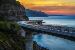 Solnedgång över havsklippabron längs det australiska Stilla havet Arkivbilder