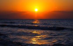 Solnedgång över havvågor Arkivfoto
