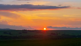Solnedgång över horisonten mot den orange himlen arkivbild