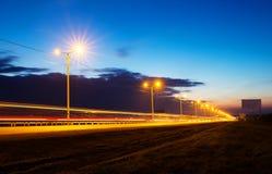 Solnedgång över huvudvägen, långt exponeringsfoto Arkivfoto