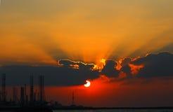 Solnedgång över industriell hamnstad Fotografering för Bildbyråer