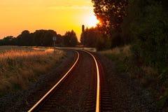 Solnedgång över järnvägar i sommartiden arkivfoto