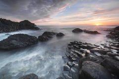 Solnedgång över jättevägbanken, norr Irland royaltyfri foto