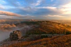 Solnedgång över kullar i moln Royaltyfria Bilder