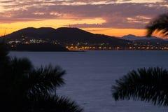 Solnedgång över kullar och vatten Arkivbilder