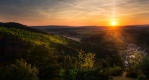 Solnedgång över kullarna och en by fotografering för bildbyråer