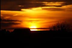 Solnedgång över kullen med små moln arkivfoton