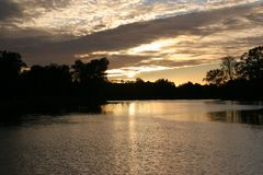 Solnedgång över laken arkivbilder
