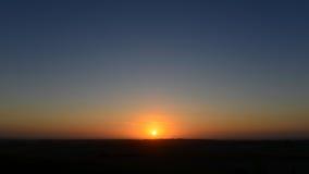 Solnedgång över land Arkivfoto