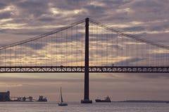 Solnedgång över 25na av April Bridge i Lissabon royaltyfria foton