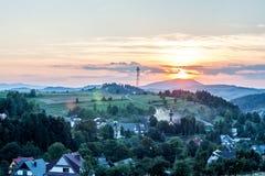 Solnedgång över by och gröna kullar Arkivbild
