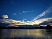 Solnedgång över sjön med moln Royaltyfri Fotografi
