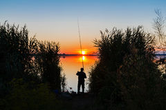 Solnedgång över sjön och fiskaren Arkivfoto