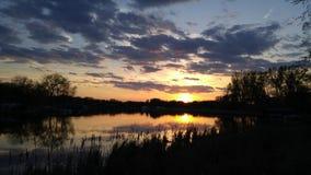 Solnedgång över sjön på skymning Arkivbild