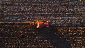 Solnedgång över skördfält med att odla traktoren Bonde som plogar stubbåkern lager videofilmer