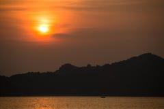 SOLNEDGÅNG över skogilskna blicken på vatten, bakgrund Arkivfoto