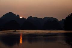 SOLNEDGÅNG över skogilskna blicken på vatten, bakgrund Royaltyfria Bilder