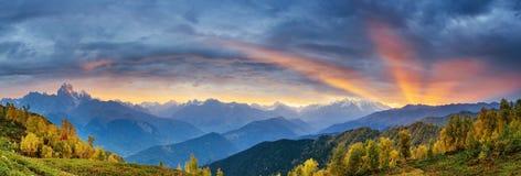 Solnedgång över snö-korkade bergmaxima Arkivfoto