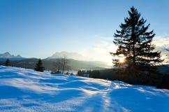 Solnedgång över snöig äng i fjällängar Arkivbild