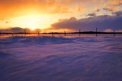 Solnedgång över snowbank Arkivbilder