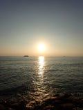 Solnedgång över Stilla havet med ljus som reflekterar på vatten och Arkivbild