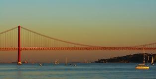 Solnedgång över Taguset River med 25 de Abril Bridge i Lissabon Royaltyfria Bilder