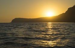 Solnedgång över udden i havet arkivfoto