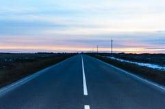 Solnedgång över vägen som täckas med asfalt, som går bort På antingen sida av ett tomt fält fotografering för bildbyråer