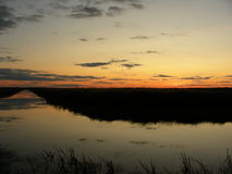 Solnedgång över vattnet, efter solnedgång, skymning, orange gryning Royaltyfria Foton