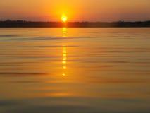 Solnedgång av en sjö Arkivfoto
