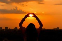 Solnedgång av flickan som fångar solen i hjärta Arkivbild