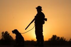 Solnedgång av jägaren med en hund Arkivfoton