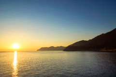 Solnedgång av kusten av Italien Arkivfoto