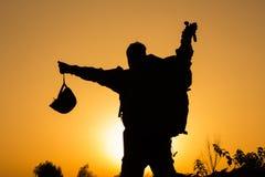 Solnedgång av soldaten i likformig med en hjälm i hand Royaltyfri Foto