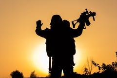 Solnedgång av soldaten som huka sig ned i likformig Fotografering för Bildbyråer