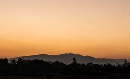Solnedgång bak berg Fotografering för Bildbyråer