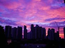 Solnedgång bak byggnader med härlig molnig himmel arkivbild