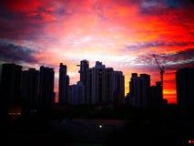 Solnedgång bak byggnader med härlig molnig himmel arkivfoton