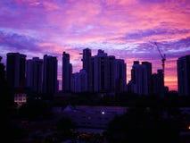 Solnedgång bak byggnader med härlig molnig himmel arkivbilder