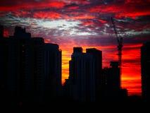 Solnedgång bak byggnader med härlig molnig himmel royaltyfri foto