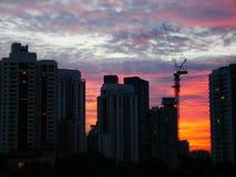 Solnedgång bak byggnader med härlig molnig himmel arkivfoto