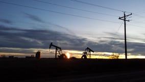 Solnedgång bak de olje- brunnarna i ND Royaltyfri Foto