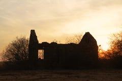 Solnedgång bak det gamla förstörda huset Royaltyfria Bilder