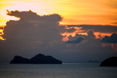 Solnedgång bak en liten holme royaltyfri fotografi