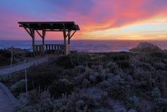 Solnedgång bak en offentlig gazebo på Asilomar den statliga stranden i Califor Arkivbild