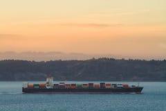 Solnedgång bak ett lastfraktbåtskepp för internationell import och export av gods arkivbild