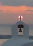 Solnedgång bak korset på ett torn för kyrklig klocka Arkivbilder